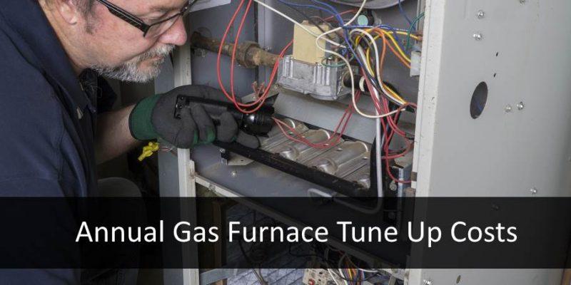 hvac service man checking furnace tune up costs maintenance